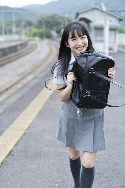 駅のホームでグレーの制服に身を包み微笑むHKT48の田島芽瑠